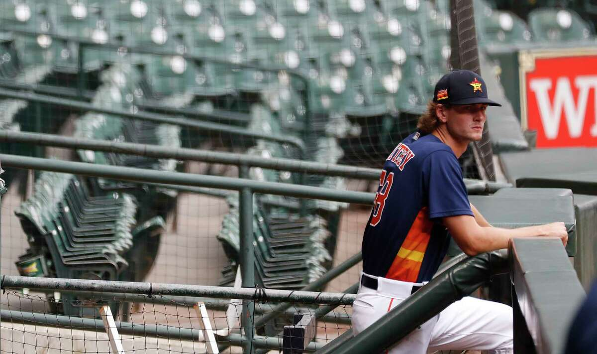 Houston Astros pitcher Forrest Whitley waits in the visitors dugout as he prepared to throw during the Astros summer camp at Minute Maid Park, Wednesday, July 8, 2020, in Houston.