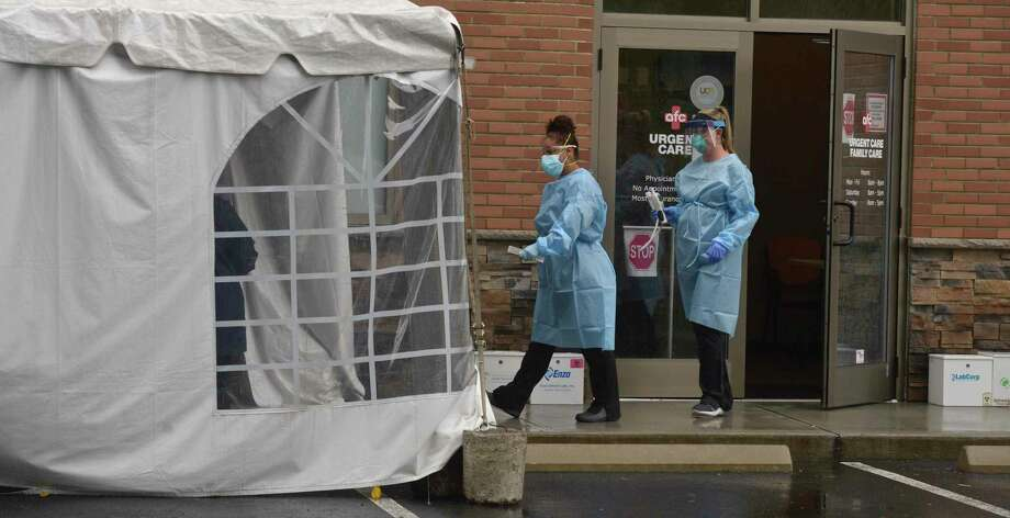 Crystal Arce, medical assistant and Jessica Bouchard, X-ray technician, go to a tented testing are to perform a SARS-COV-2 test at AFC Urgent Care, Wednesday, July 8, 2020, in Danbury, Conn. Photo: H John Voorhees III / Hearst Connecticut Media / The News-Times