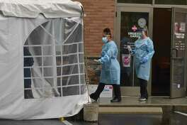 Crystal Arce, medical assistant and Jessica Bouchard, X-ray technician, go to a tented testing are to perform a SARS-COV-2 test at AFC Urgent Care, Wednesday, July 8, 2020, in Danbury, Conn.