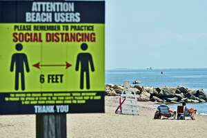 A sign reminds visitors of social distancing measures at the town beach in East Haven Wednesday.