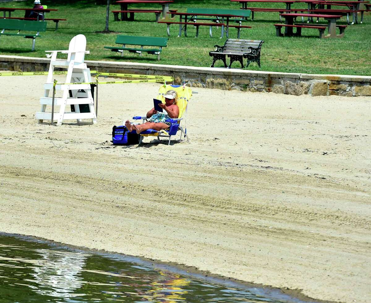 A sunbather reads on the beach at Branford Point in Branford Wednesday.