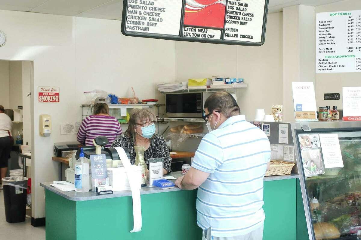 Cecy Garcia prepares a sandwich as Dixie Deli owner Donna Bullard takes an order from Pierre Matta.