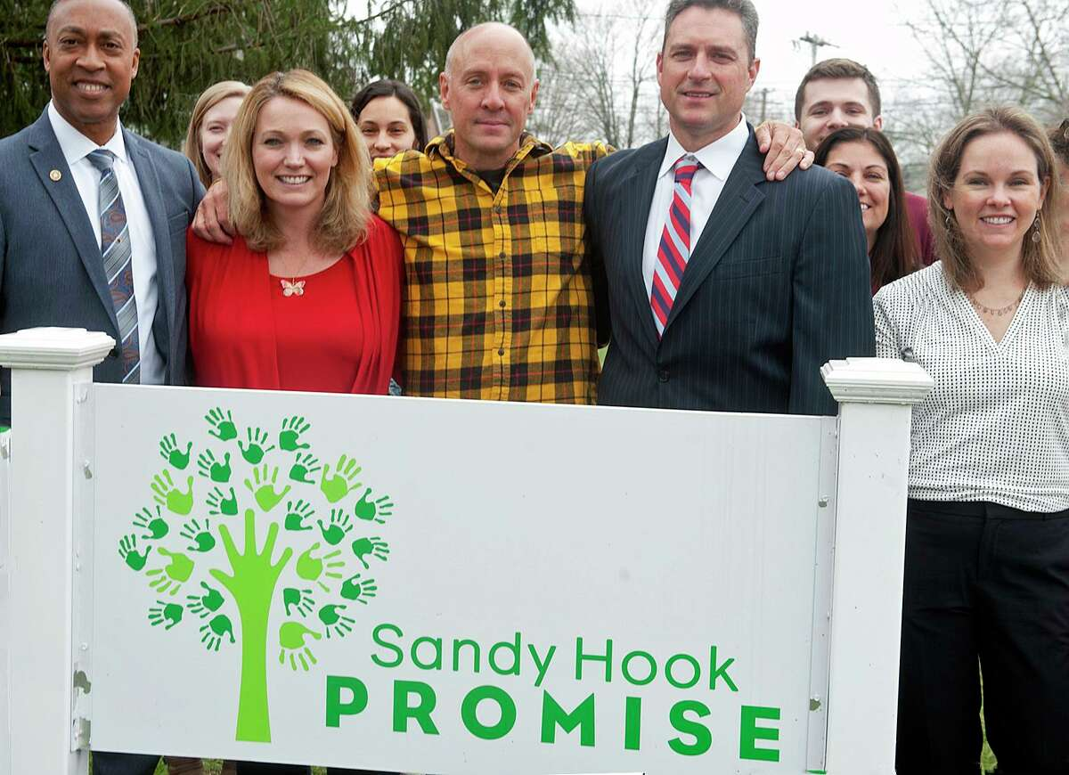 Robert Fuller, right, Assistant Special Agent in Charge of the FBI's New Haven Field Office and Charles Grady, left, an FBI Community Outreach Specialist, stand with Nicole Hockley, Mark Barden and others from Sandy Hook Promise in Newtown, Conn. April 8, 2019. Sandy Hook Promise was among the greater Danbury employers to receive a coronavirus relief check from the Small Business Administration.