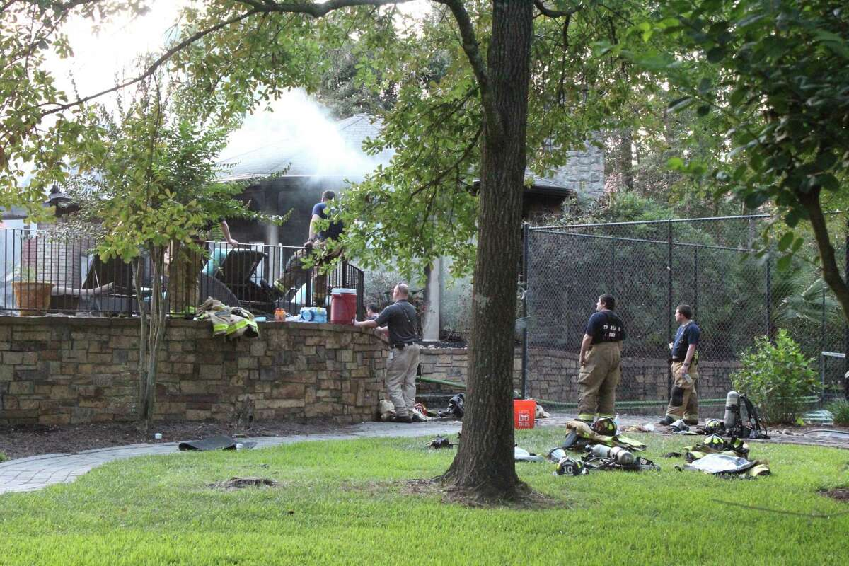 The Woodlands Fire Department continues to confront the COVID-19 novel coronavirus, with a reported total of five firefighters testing positive for the coronavirus and 15 total staff in quarantine as of July 8. Previously there were three positive tests and eight firefighters in quarantine. In this file photograph, firefighers battle the remains of a house fire in the Village of Cochran's Crossing, adjacent to the third hole of The Woodlands Country Club Palmer golf course.