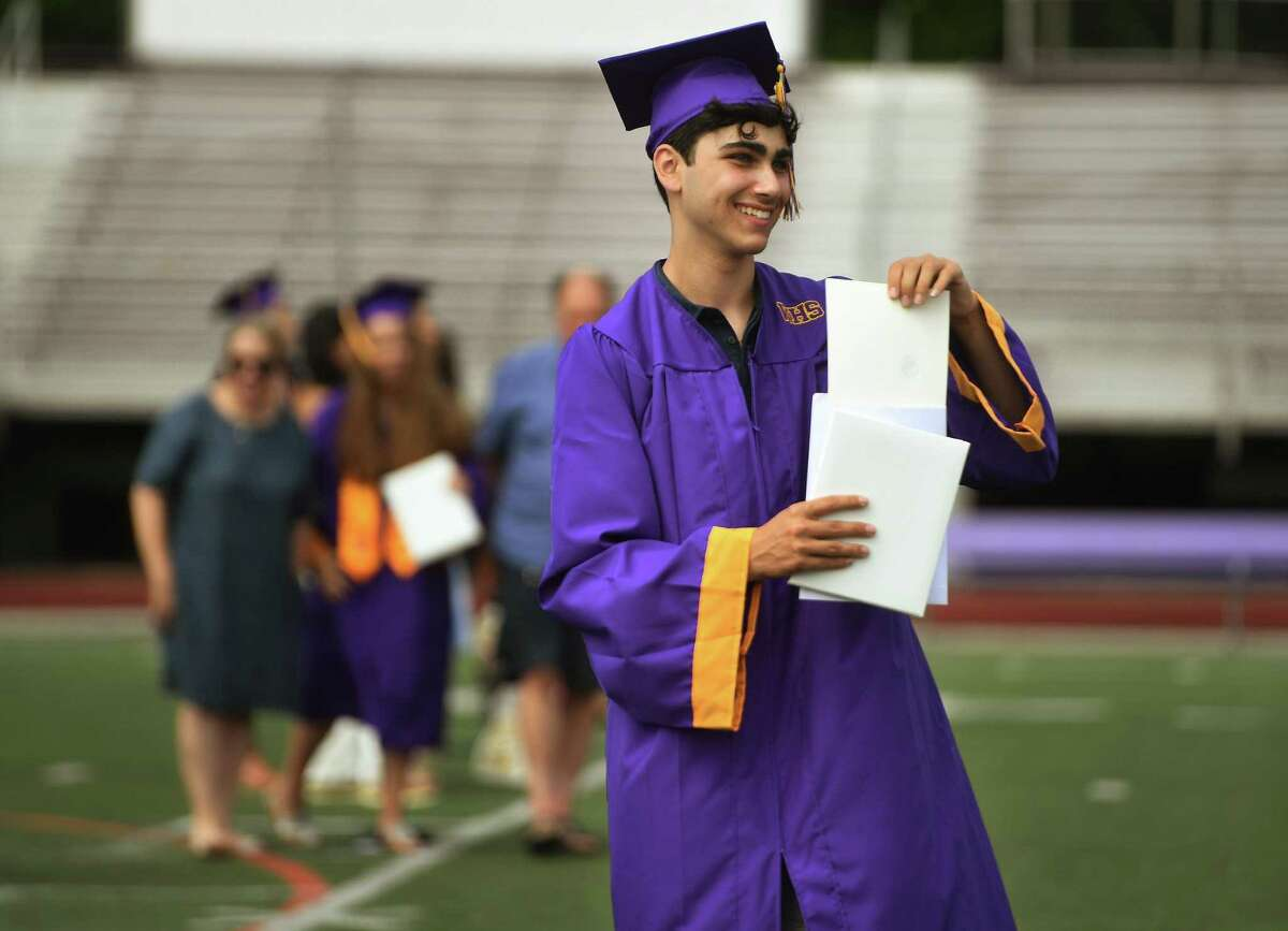Westhill High graduate Oren Gabay shows off his diploma to fellow grads during a socially distanced graduation ceremony at the school on Wednesday.