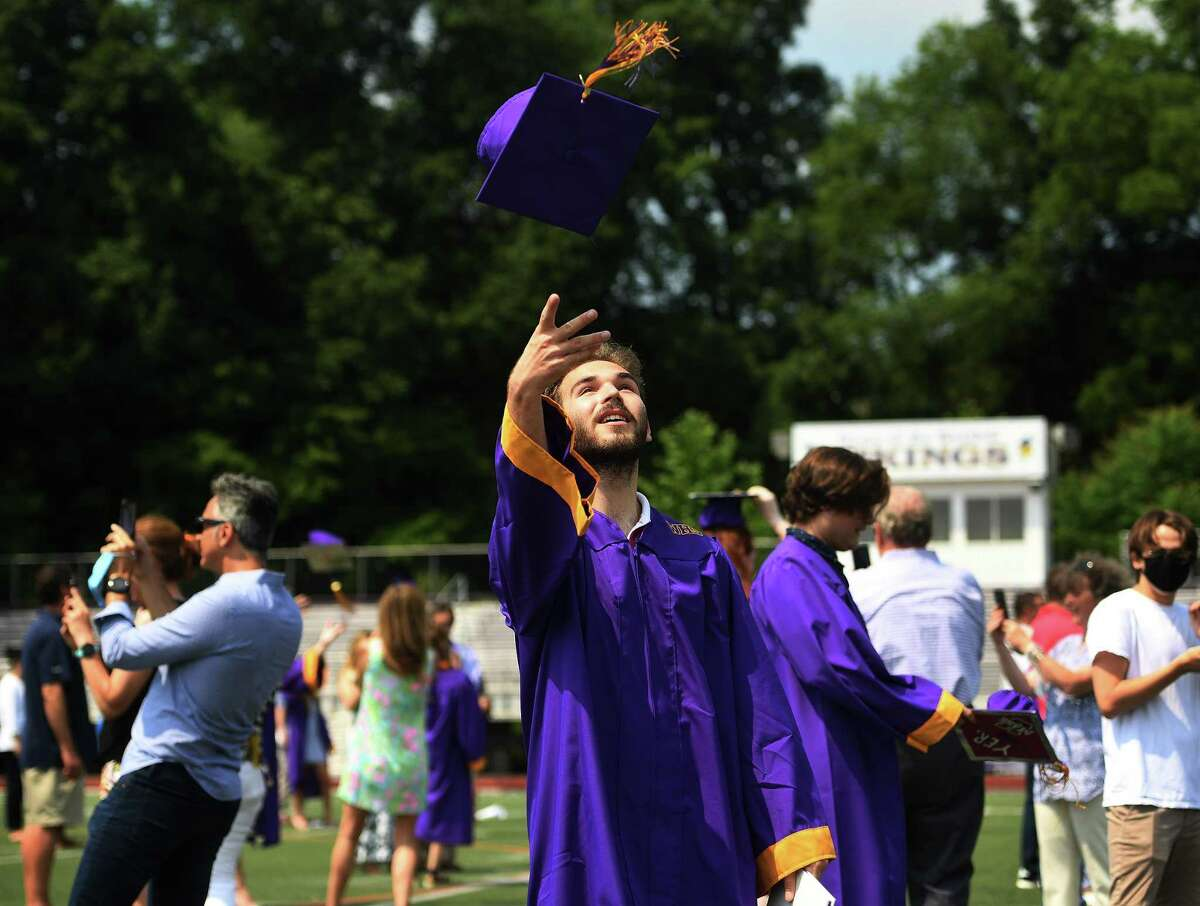 Westhill High graduate Lucca Metzger tosses his mortarboard in the air at the conclusion of a socially distanced graduation ceremony at the school in Stamford, Conn. on Wednesday, July 8, 2020.