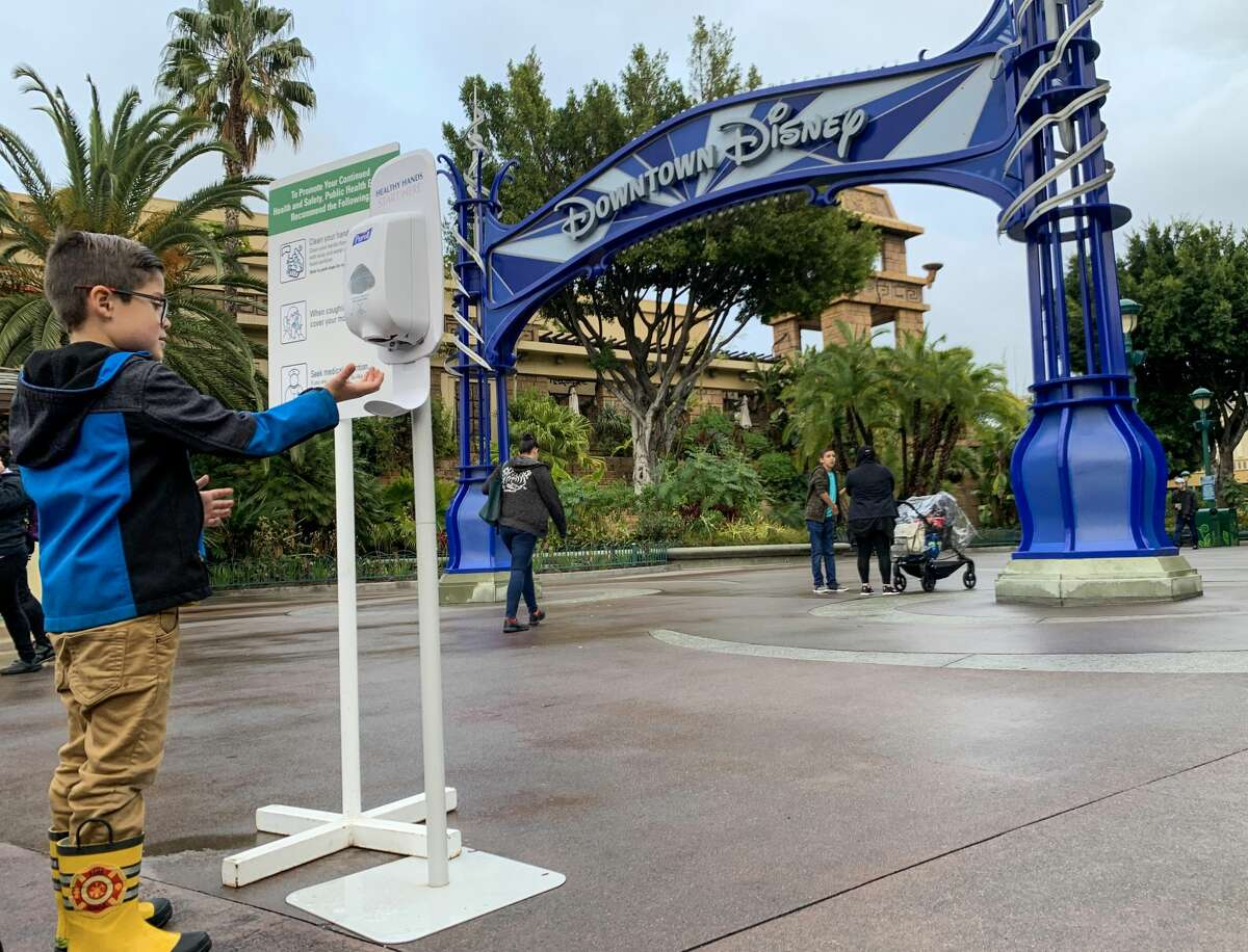 A young visitor to Downtown Disney uses a hand sanitizer station during the day last before Disneyland closes because of the coronavirus (COVID-19) outbreak in Anaheim, CA, on Friday, March 13, 2020.
