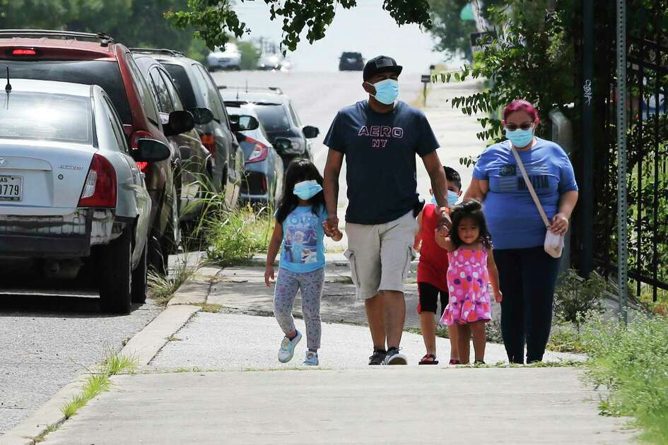 Lytle residents Enrique and Veronica Hernandez and their children walk to Kazen Middle School, 1520 Gillette, to get tested for the novel coronavirus on Monday. Veronica had mentioned that she and her husband were experiencing some symptoms and wanted to get tested. Officials at the location said there were between 200-300 people waiting when the site opened at 10 a.m. 800 tests are available at the walk-up testing center where people actually administer their own oral test for the virus. The no-cost testing location will remain open until the end of the month.