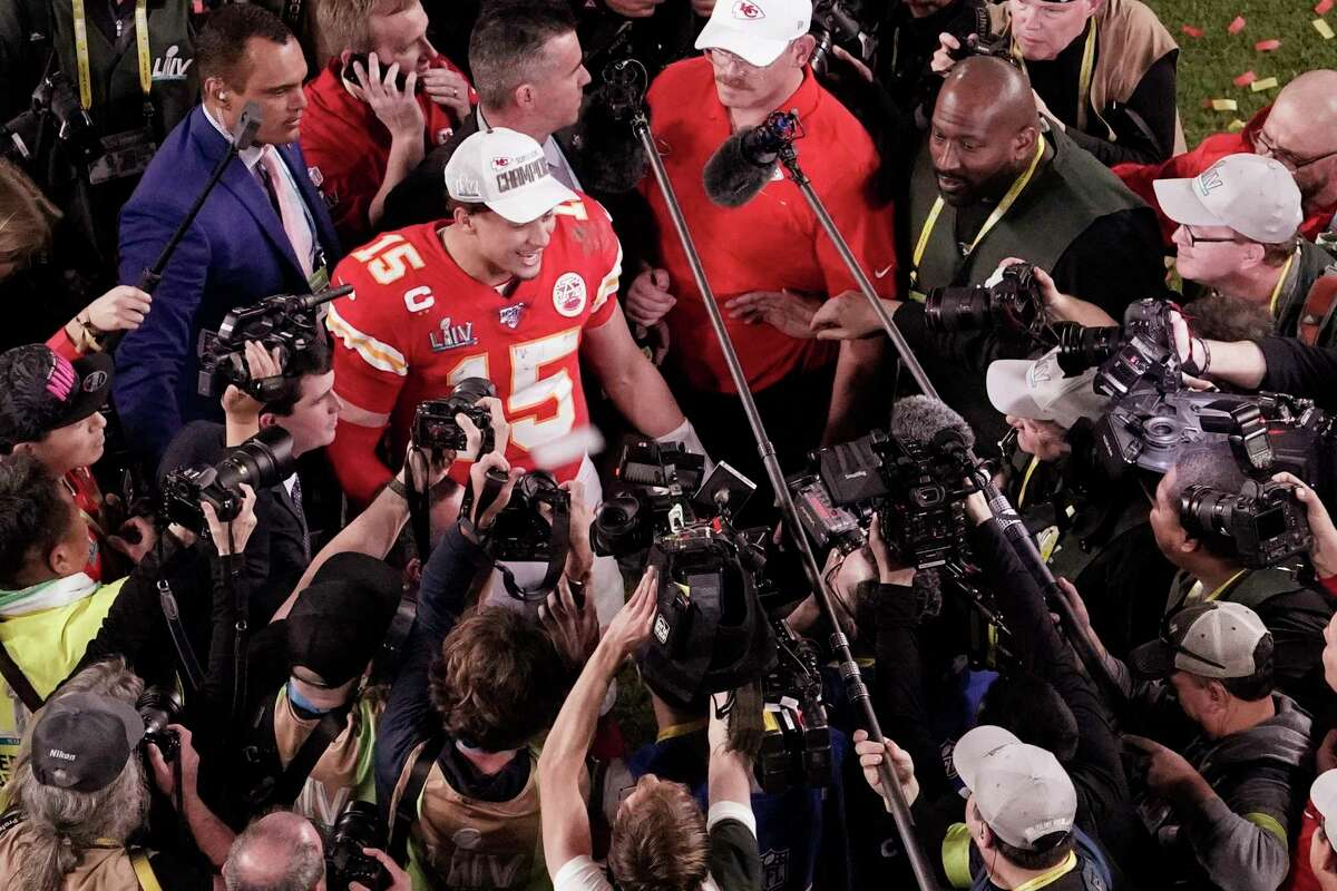 FILE - In this Feb. 2, 2020, file photo, Kansas City Chiefs quarterback Patrick Mahomes (15) is surrounded by media after his team won the NFL Super Bowl 54 football game against the San Francisco 49ers, in Miami Gardens, Fla. As sports prepare to resume, journalists are facing the same reckoning that their colleagues who cover politics, education and entertainment have encountered a€?