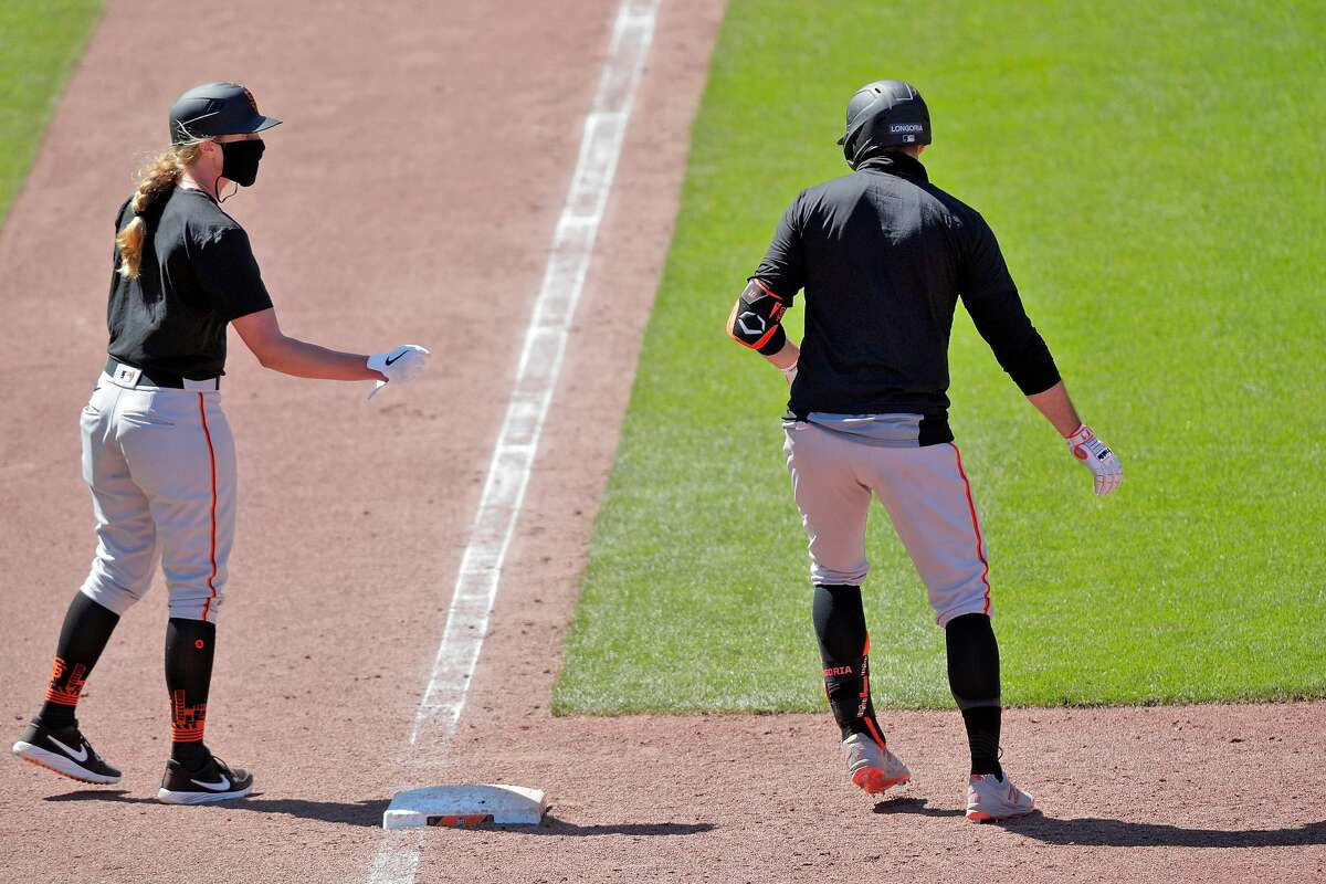 Alyssa Nakken, coaching first, talks wtih Evan Longoria during the game as the San Francisco Giants worked out and played a simulated game at Oracle Park in San Francisco, Calif., on Wednesday, July 8, 2020.