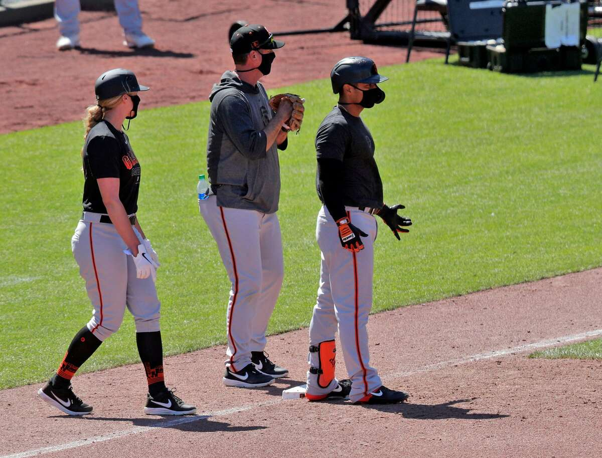 Alyssa Nakken, coaching first, approaches the runner as the San Francisco Giants worked out and played a simulated game at Oracle Park in San Francisco, Calif., on Wednesday, July 8, 2020.