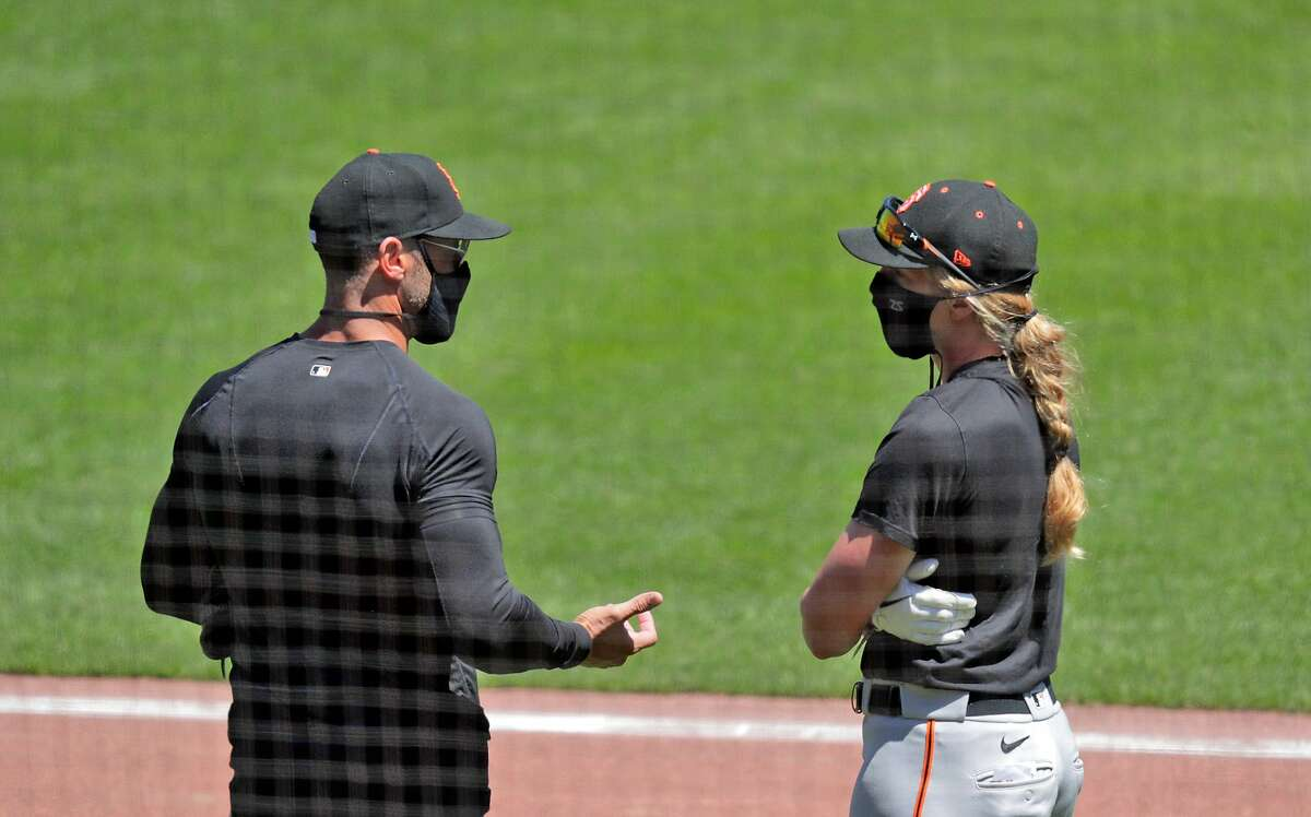 Alyssa Nakken, right, chats wtih Giants manager Gabe Kapler as the San Francisco Giants worked out and played a simulated game at Oracle Park in San Francisco, Calif., on Wednesday, July 8, 2020.
