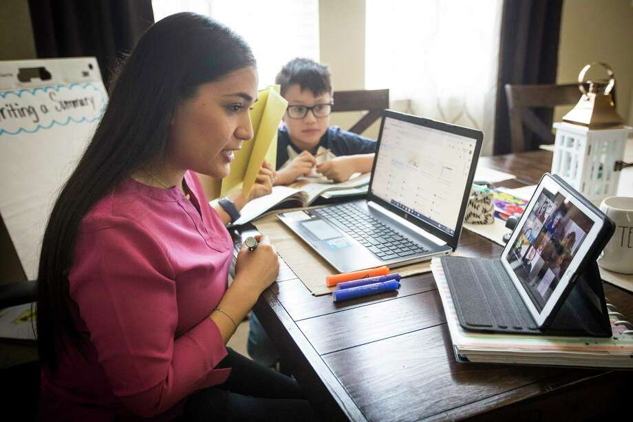 Royalwood Elementary School fourth-grader teacher Elizabeth Ortega, pictured in March, talks to her Sheldon ISD students as she delivers a lesson from her dining room table in Friendswood. Educators widely acknowledge that virtual-only classes are inferior to in-person instruction, though returning to school buildings increases the risk of spreading the novel coronavirus. Photo: Brett Coomer, Houston Chronicle / Staff Photographer / © 2020 Houston Chronicle