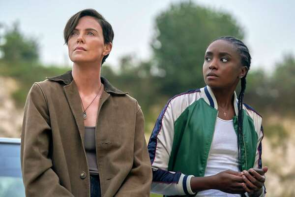 """This image released by Netflix shows Charlize Theron, left, and Kiki Layne in a scene from """"The Old Guard,"""" premiering July 10 on Netflix. (Aimee Spinks/Netflix via AP)"""