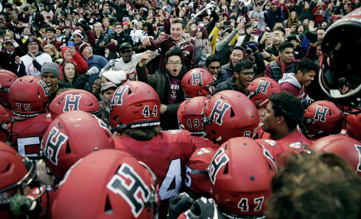 FILE - In this Nov. 17, 2018, file photo, Harvard players, students and fans celebrate their 45-27 win over Yale after an NCAA college football game at Fenway Park in Boston. Harvard defeated Yale. The Ivy League has canceled all fall sports because of the coronavirus pandemic. (AP Photo/Charles Krupa, File)