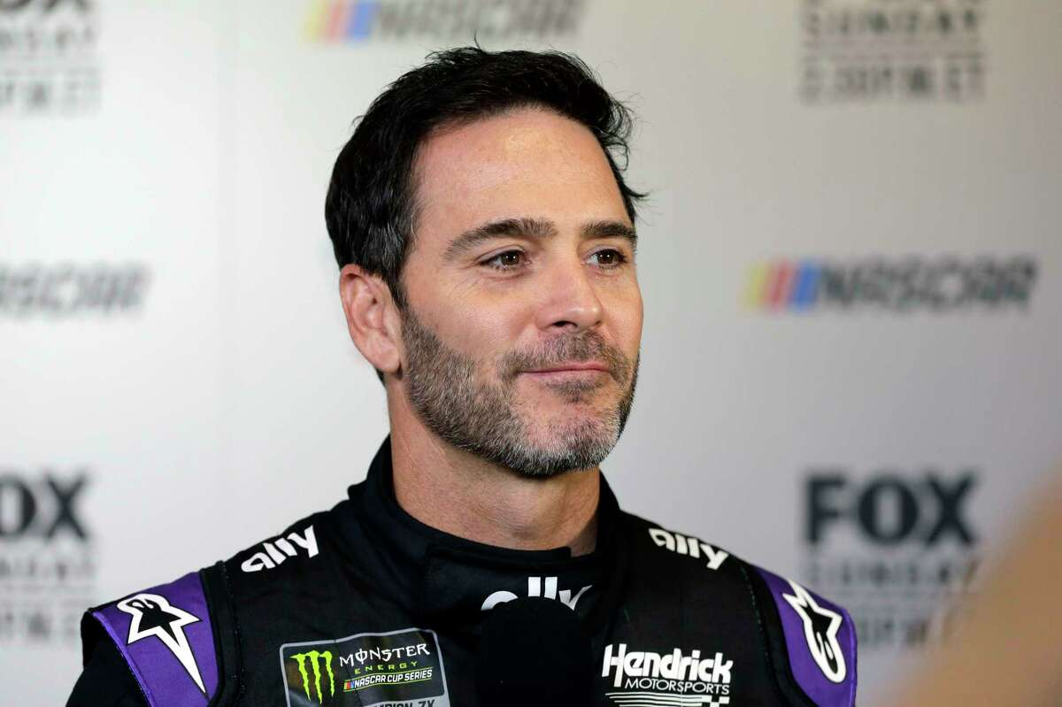 FILE - In this Feb. 13, 2019, file photo, driver Jimmie Johnson smiles during media day for the NASCAR Daytona 500 auto race at Daytona International Speedway in Daytona Beach, Fla. Seven-time NASCAR champion Jimmie Johnson has twice tested negative for the coronavirus and has been cleared to race Sunday, July 12, 2020 at Kentucky Speedway. Johnson missed the first race of his Cup career when he tested positive last Friday. (AP Photo/Terry Renna, File)