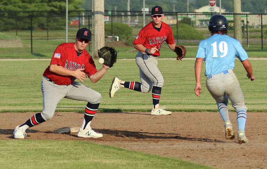 Alton second baseman Gage Booten (left) takes a throw before tagging out Jersey's Ian Sullivan (19), who is caught stealing while Alton shortstop Cullen McBride backs up the play Wednesday night at Ken Schell Field in Jerseyville. Photo: Greg Shashack | The Telegraph
