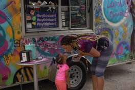 Houston - Bobbie Hoskins, 24, leans in to give a kiss to her daughter, Aten Gasper, 2. The two came out to support Earthy Goodness and Soul Food Vegan for the national Blackout Day (HC).