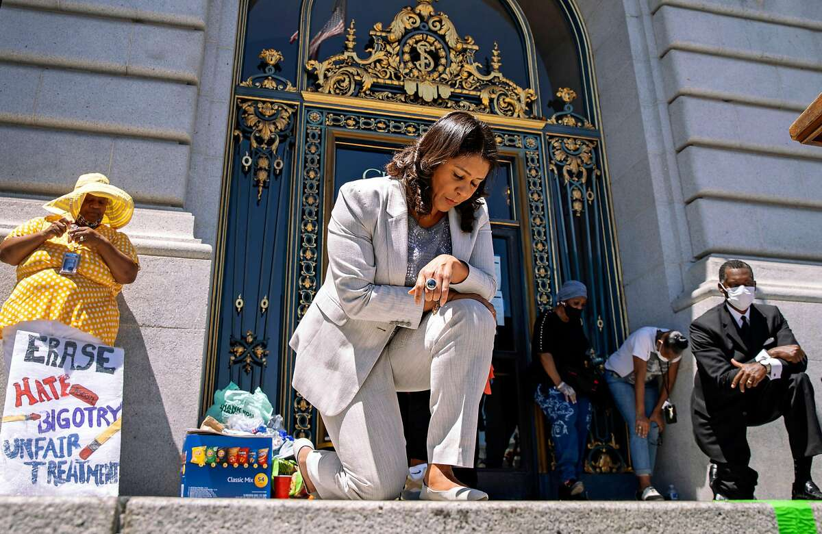 In honor of George Floyd, San Francisco Mayor London Breed takes a knee for eight minutes and 46 seconds with thousands of people during a rally at City Hall, Tuesday, June 9, 2020, in San Francisco, Calif.