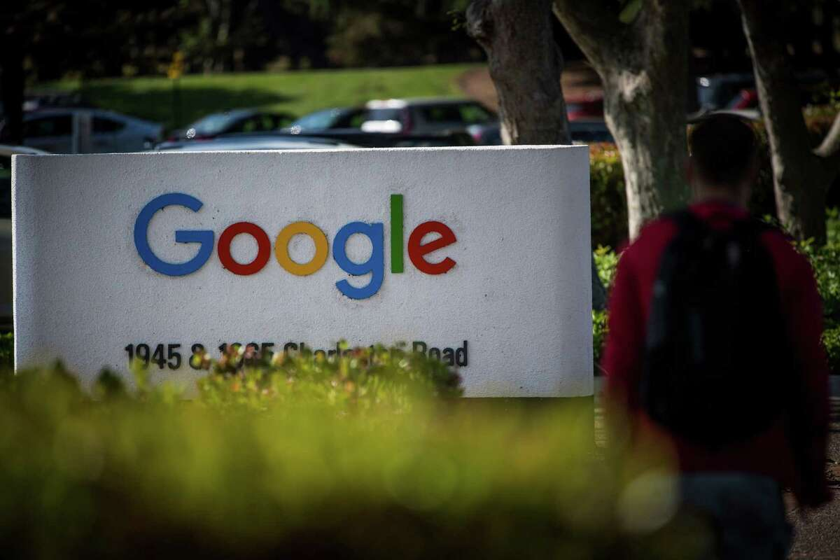 A pedestrian walks a Google Inc. sign at the company's headquarters in Mountain View, Calif., on April 25, 2018.