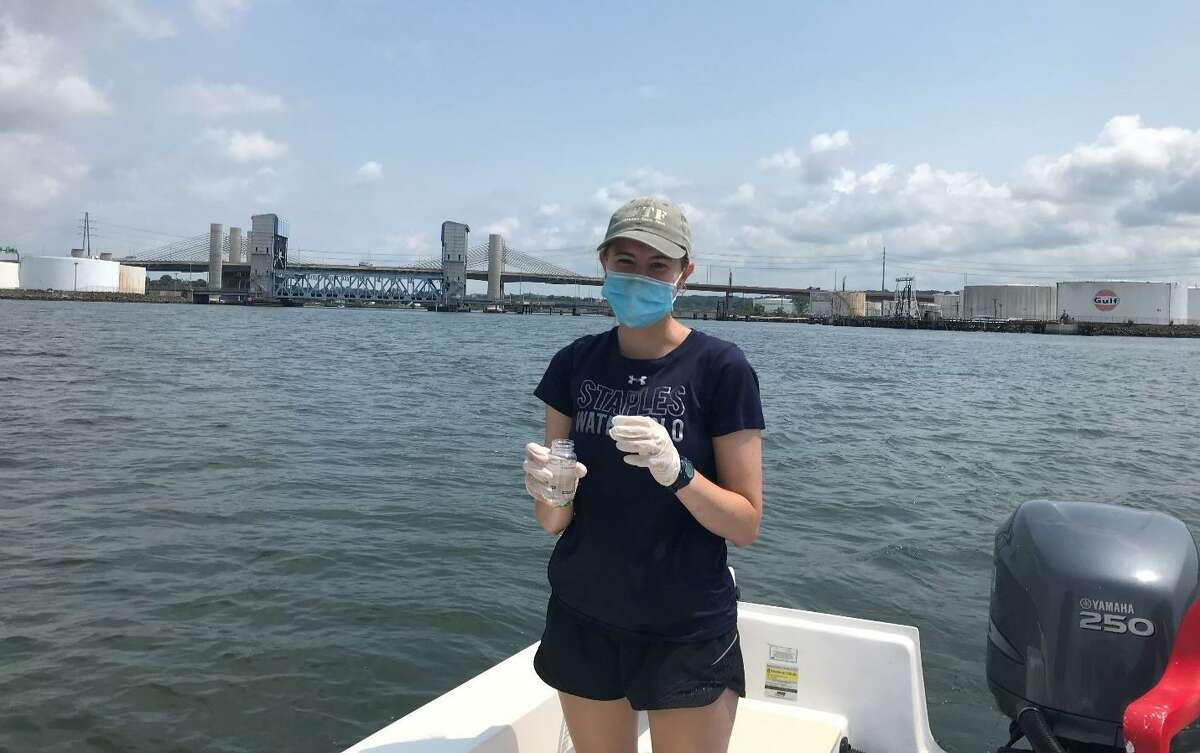 Save the Sound intern Teagan Smith collects water samples in New Haven Harbor with Soundkeeper Bill Lucey Wednesday.