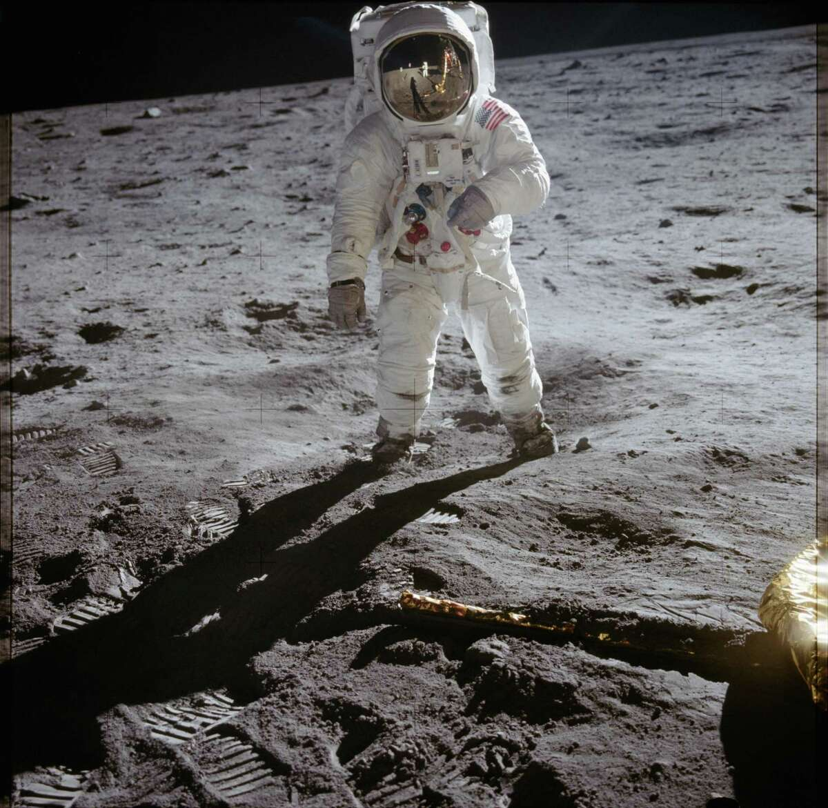 """On July 20, 1969, astronaut Buzz Aldrin walks on the surface of the moon near the leg of the Lunar Module """"Eagle"""" during the Apollo 11 extravehicular activity. Astronaut Neil Armstrong took this photograph with a 70mm lunar surface camera."""