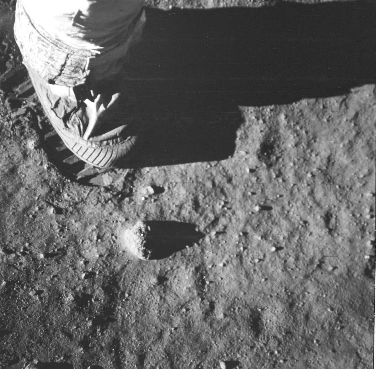 This is a close-up view of an astronaut's foot and footprint in the lunar soil, photographed during the Apollo 11 lunar surface extravehicular activity.