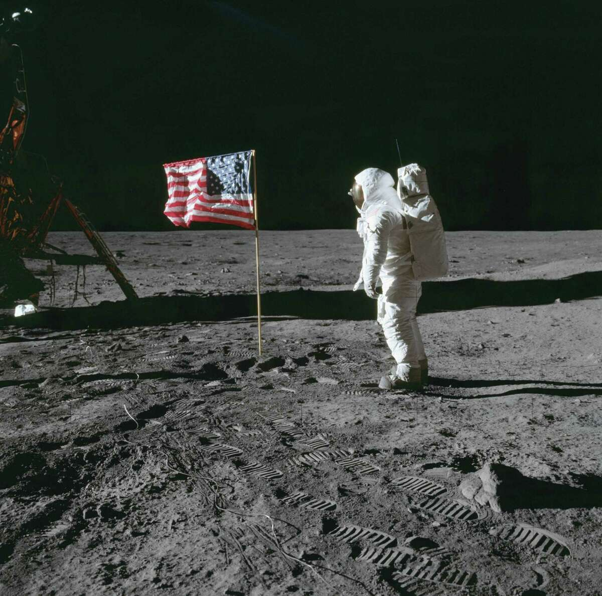On July 20, 1969, astronaut Buzz Aldrin beside the deployed United States flag during Apollo 11 extravehicular activity on the lunar surface. The Lunar Module is on the left, and the footprints of the astronauts are clearly visible in the soil of the moon.