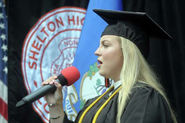Kyla Hackett sings the National Anthem during the first of three graduation ceremonies held Wednesday for the Shelton High School Class of 2020, in Shelton, Conn. July 8, 2020.