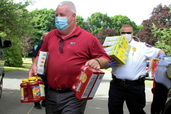 State Rep. Ben McGorty (left) assists during a food drive in Shelton, Conn., on July 1, 2020. Increasing numbers of Connecticut residents filed for unemployment assistance the first week of July, putting the statewide total at about 253,000 people receiving aid as of July 4.