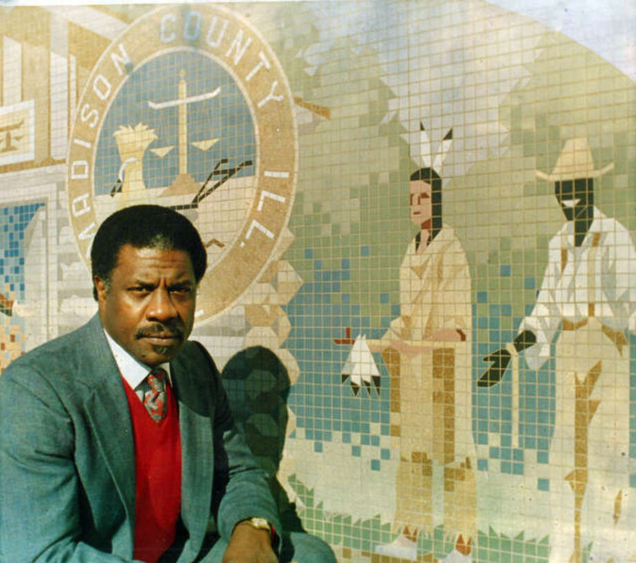 Herman Shaw poses in front of a mural at Edwardsville City Hall that black residents felt was stereotypical. Shaw led the effort to get the mural changed in 1987. Photo: For The Intelligencer
