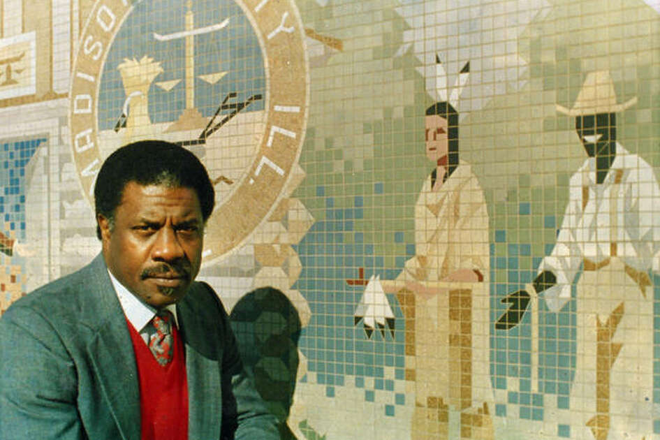 Herman Shaw poses in front of a mural at Edwardsville City Hall that black residents felt was stereotypical. Shaw led the effort to get the mural changed in 1987.