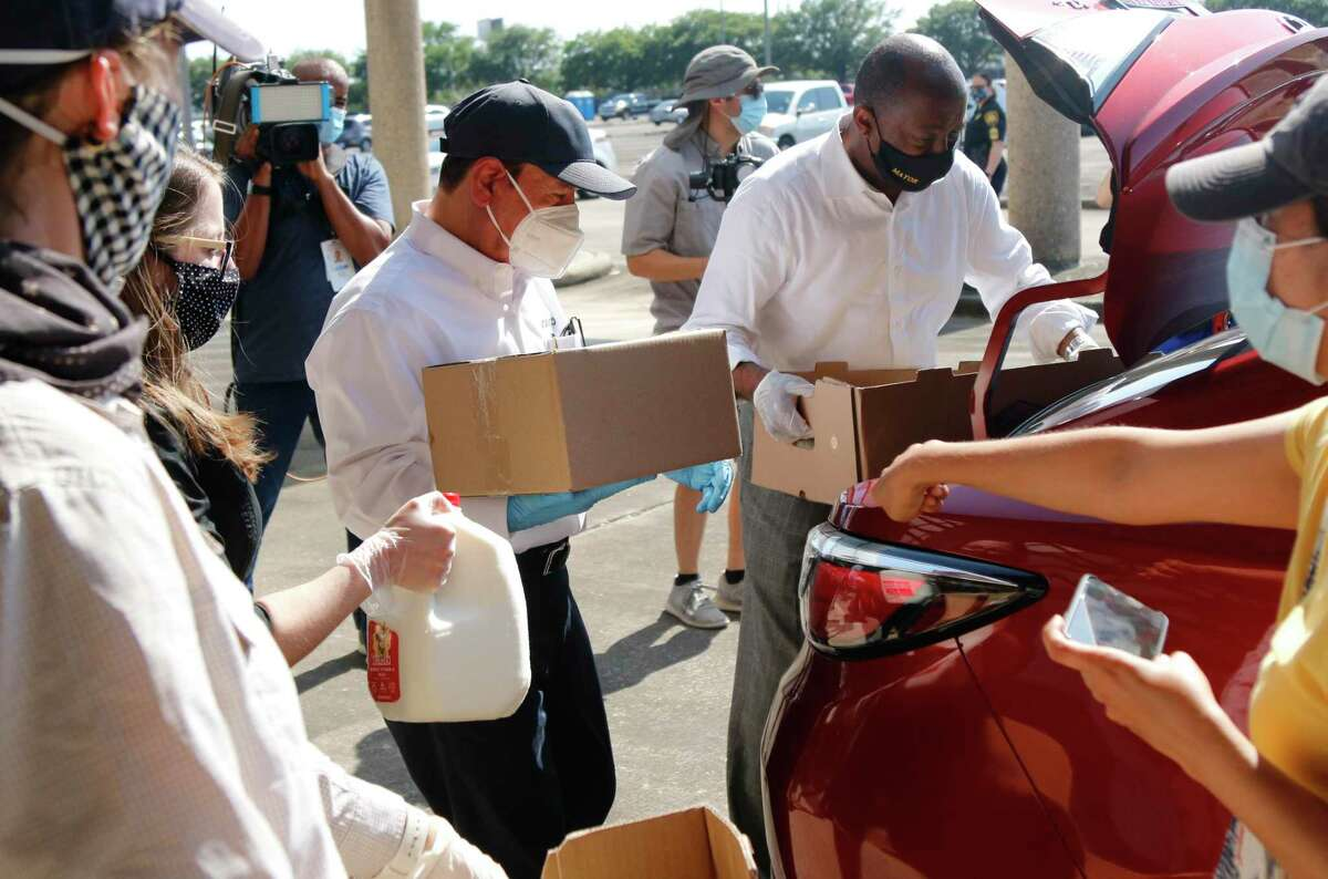Aramco America's President & CEO Mohammad Alshammari, left, and Houston Mayor Sylvester Turner place food distribution items into the back of a vehicle as Texas State Representative Anna Eastman and the Houston Food Bank hosted a food distribution drive serving Houston's Northwest community Tuesday at at the former Park and Ride facility on Pinemont and Federal Plaza Drive serving about 2,200 families. Joining Eastman were Houston Mayor Sylvester Turner, Aramco Americas CEO and President Mohammad S. Alshammari, along with about 90 volunteers from Aramco and their family members. The volunteers served the drive-up attendees with free groceries, masks and hand sanitizer.