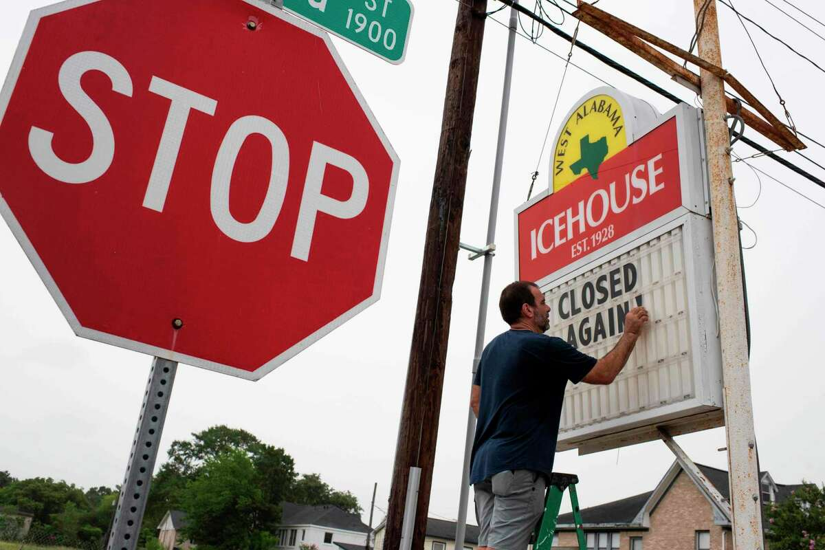 """Bar owner Petros J Markantonis changes the marquee outside his bar to """"Closed Again"""" at the West Alabama Ice House in Houston, Texas on June 26, 2020. Texas Governor Greg Abbott ordered bars to close amid a surge in coronavirus cases."""