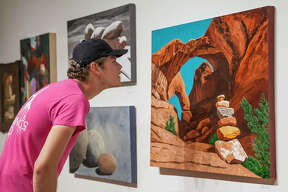"Jordan Bruce eyes a still-life painting by artist Garry McMichael inside Jacoby Arts Center's main gallery at 627 E. Broadway during the ""Balance"" exhibition, currently on display through Aug. 16."