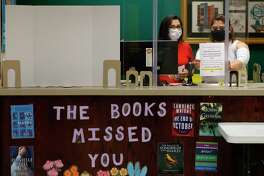 Susan Daniels, left, helps Angela Herrera post a sign telling customers the library won't be accepting fines until further notice as staff reopened the Montgomery County Central Library to the public, Wednesday, May 13, 2020, in Conroe.