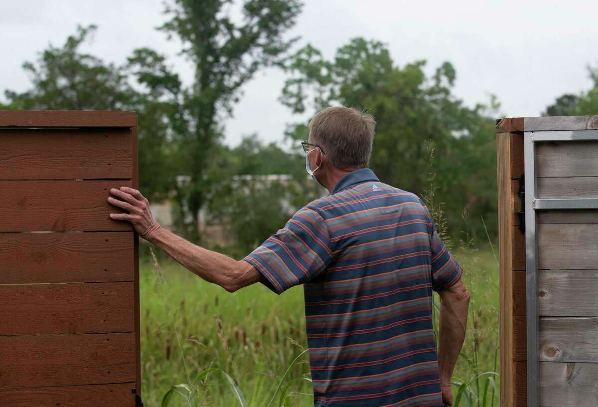 Jim Estes, looks out of his backyard fence, toward the field where an oil company recently drilled a well, on Monday, June 29, 2020, in League City, Texas.