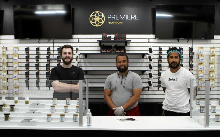 From left, Anthony Hasson, Ken Bryant and Mack Klinkman, managers of Premiere Provisions, pose in front of a variety of medical marijuana products their store will offer to patients. Premiere Provisions is set to open at 10 a.m. Saturday. Photo: Pioneer Photo/Bradley Massman