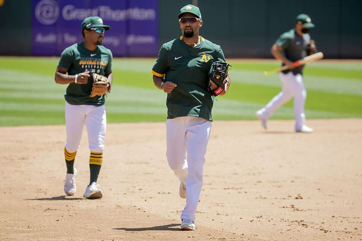Oakland A's infielder Marcus Semien (center) and outfielder Tony Kemp practice during an Oakland A's training camp workout at O.Co Coliseum in Oakland, Calif. Tuesday, July 7, 2020. Due to COVID-19, the 2020 MLB season has been postponed with players just beginning to return for warmups and practices while wearing masks and keeping social distance.