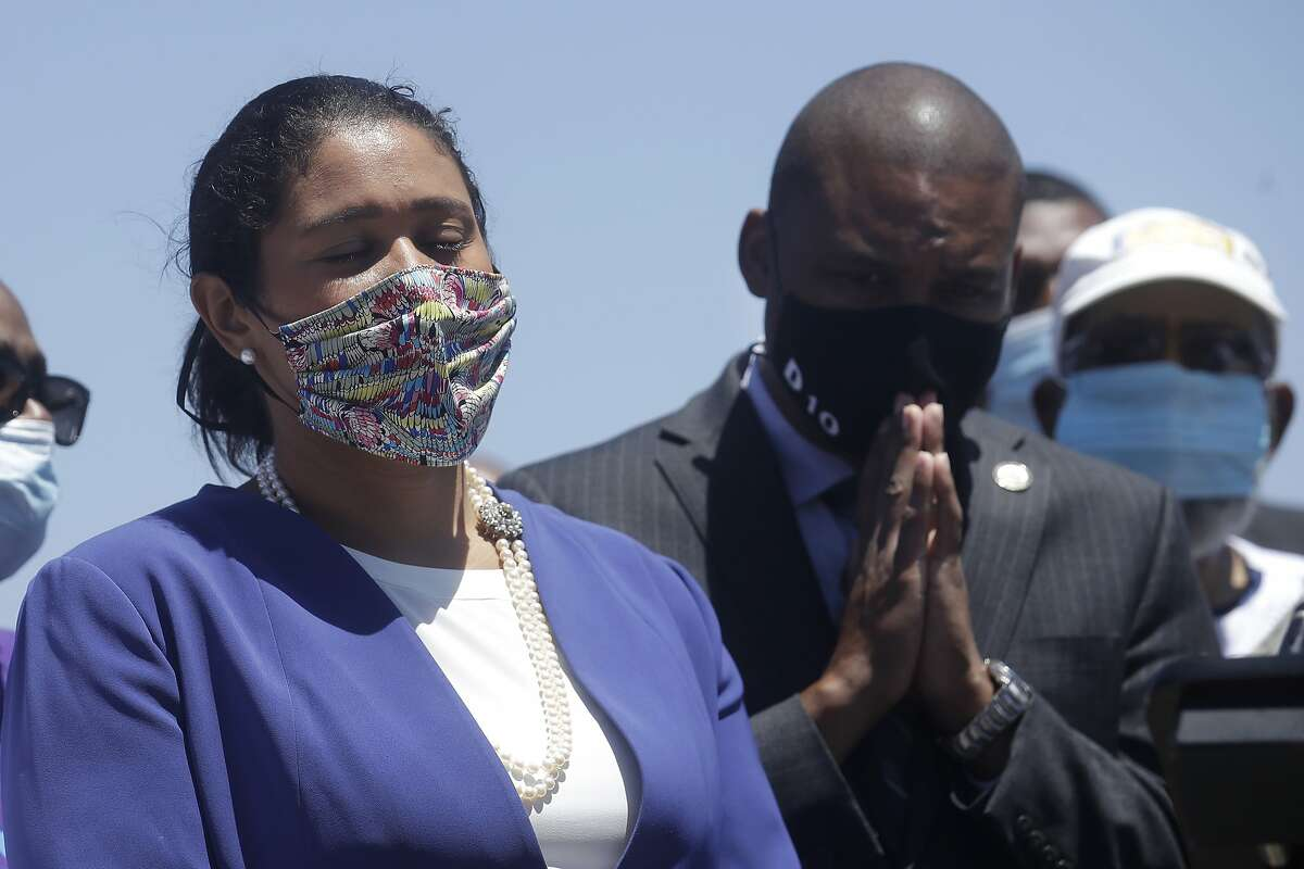 Mayor London Breed, left, and Supervisor Shamann Walton listen at a news conference about the shooting death of Jace Young in San Francisco, Tuesday, July 7, 2020. (AP Photo/Jeff Chiu)