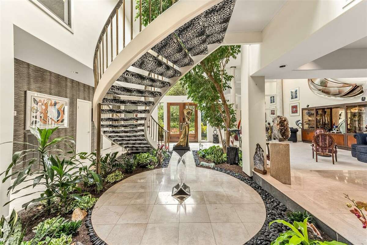 A floating stair case ascends to the landing with treetop views of the living area.
