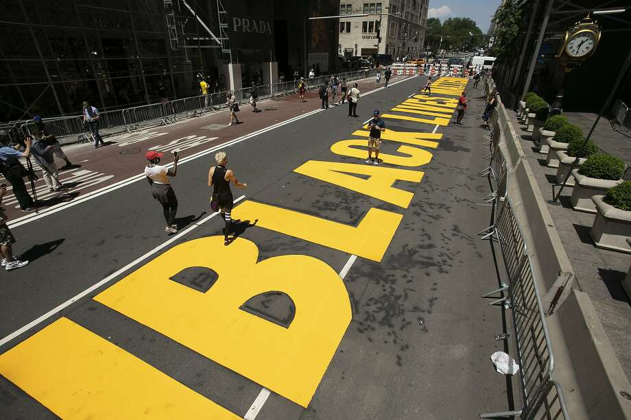 Volunteers walk along a Black Lives Matter mural that was painted on Fifth Avenue in front of Trump Tower, Thursday, July 9, 2020, in New York. (AP Photo/Mark Lennihan) Photo: Mark Lennihan, Associated Press