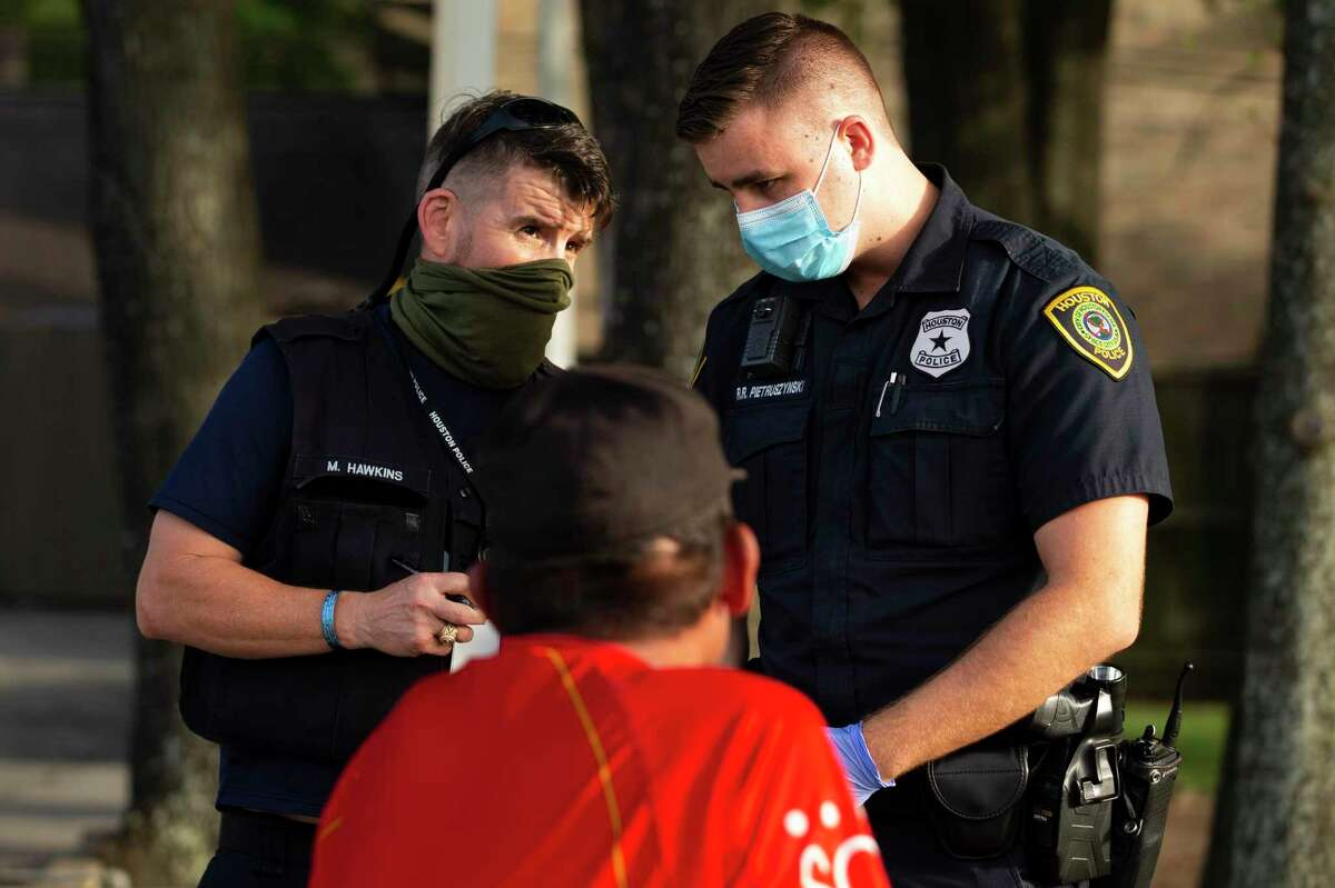 Social worker Michael Hawkins, left, and Houston Police Department Crisis Intervention Response Team Officer Richard Pietruszynski have a conversation while responding to a mental health crisis call Thursday, July 2, 2020, in Houston. The person with mental health history had been drinking straight vodka for more than 12 hours when the police arrived the scene. In Houston and Harris County, social workers have been part of the police response for more than a decade, partnering with patrol officers to respond to mental health crises and domestic violence calls.