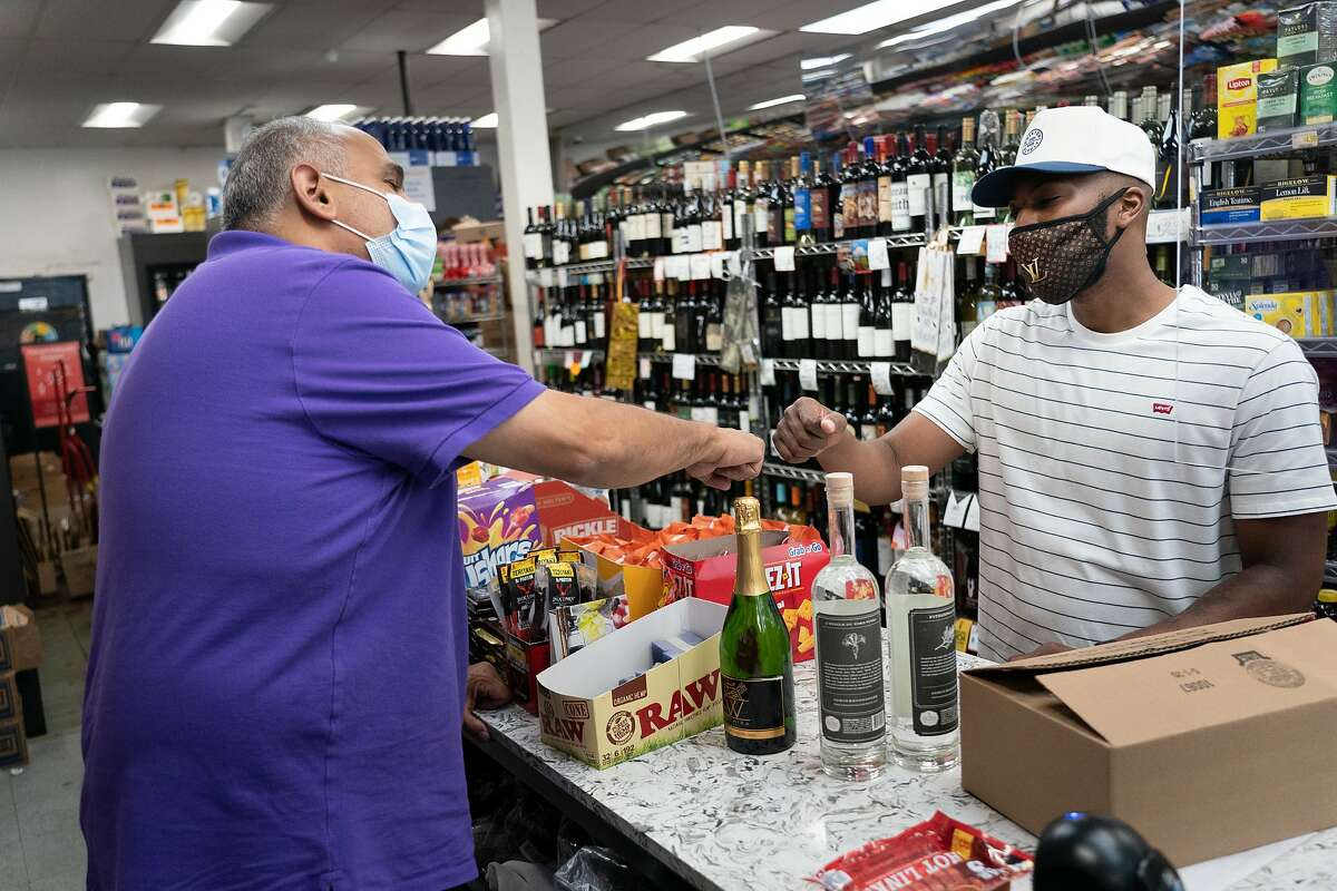Victor Oliver, right, who was laid off as a bar manager, pitches his liquid products to Telegraph Wine and Spirits owner Mo Hassan on Wednesday, July 8, 2020 in Oakland, Calif.