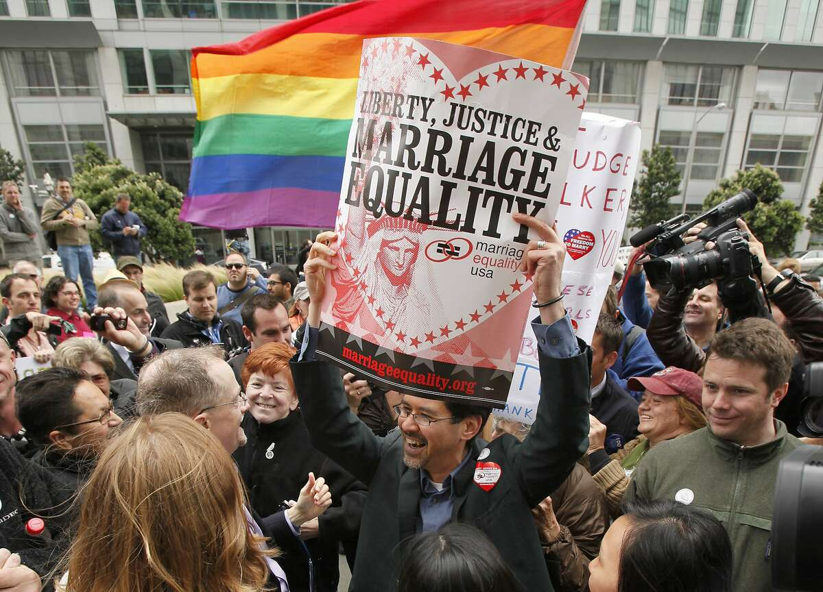 Stuart Gaffney, center, holds up a sign while celebrating the decision in the United States District Court proceedings challenging Proposition 8 outside of the Phillip Burton Federal Building in San Francisco, Wednesday, Aug. 4, 2010. A person close to the case says a federal judge has overturned California's same-sex marriage ban in a landmark case that could eventually land before the U.S. Supreme Court. Chief U.S. District Judge Vaughn Walker made his ruling Wednesday in a lawsuit filed by two gay couples who claimed the voter-approved ban violated their civil rights. (AP Photo/Eric Risberg)