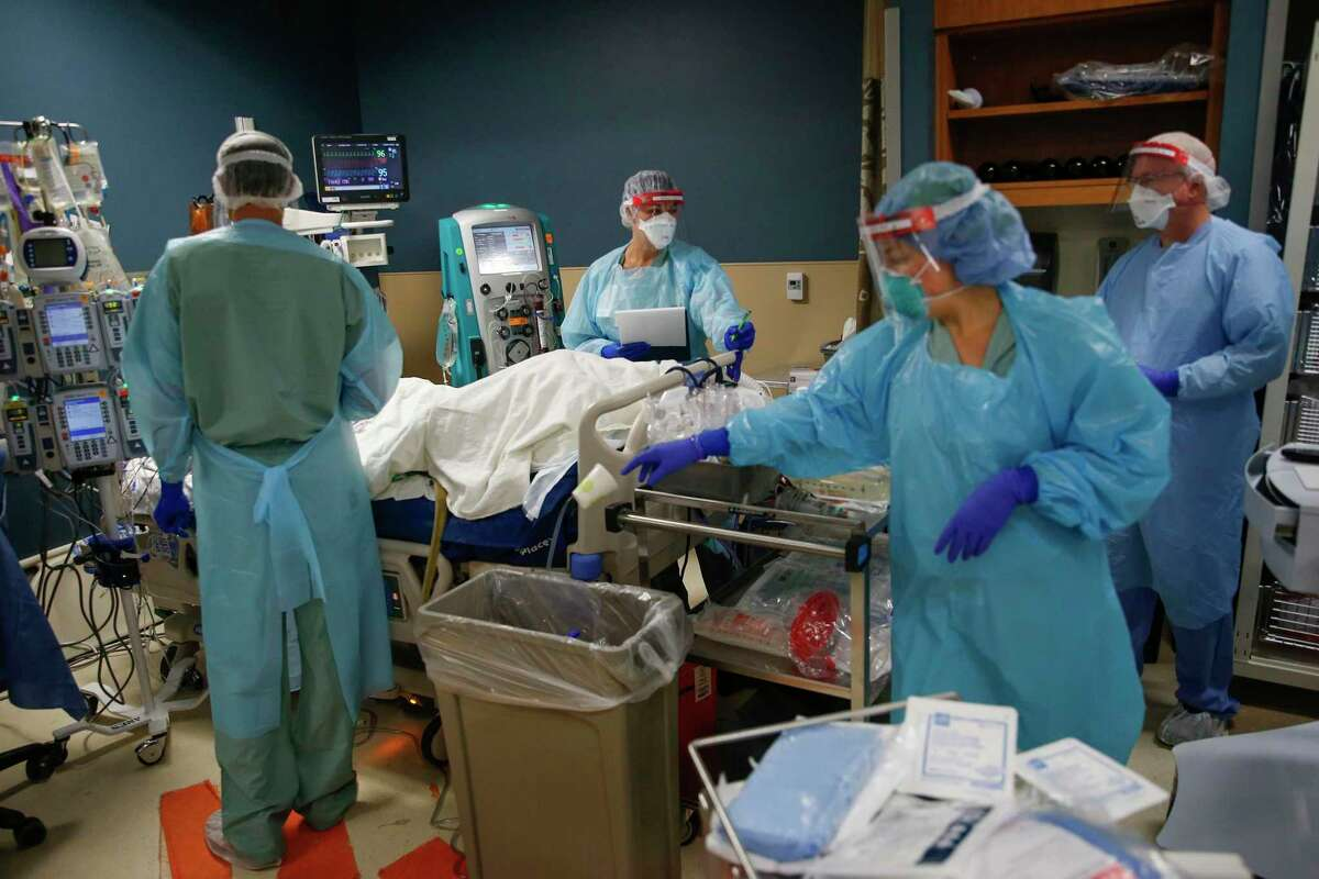 Led by Dr. Matt Leveno, left, a team of healthcare workers assesses an intubated patient in the Parkland Hospital COVID-19 Tactical Care Unit on June 27, 2020, in Dallas. (Ryan Michalesko/Dallas Morning News/TNS)