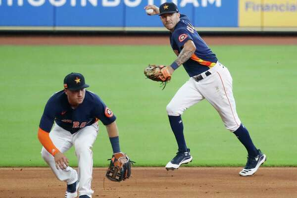 Houston Astros shortstop Carlos Correa makes the throw over third baseman Alex Bregman to get Jack Mayfield out at first base in the fourth inning of an intrasquad game during the Astros summer camp at Minute Maid Park, Thursday, July 9, 2020, in Houston.