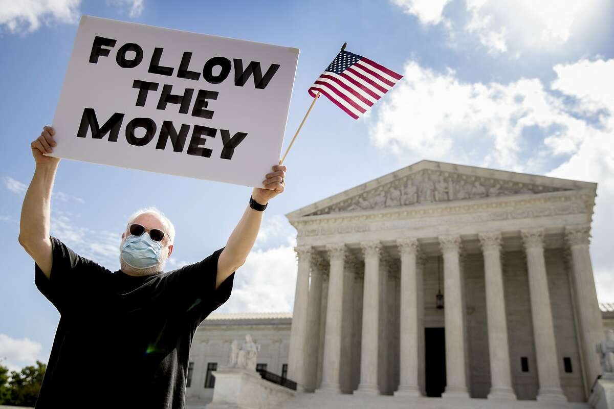 """Bill Christeson holds up a sign that reads """"Follow the Money"""" outside the Supreme Court, Thursday, July 9, 2020, in Washington. The Supreme Court ruled Thursday that the Manhattan district attorney can obtain Trump tax returns while not allowing Congress to get Trump tax and financial records, for now, returning the case to lower courts. (AP Photo/Andrew Harnik)"""