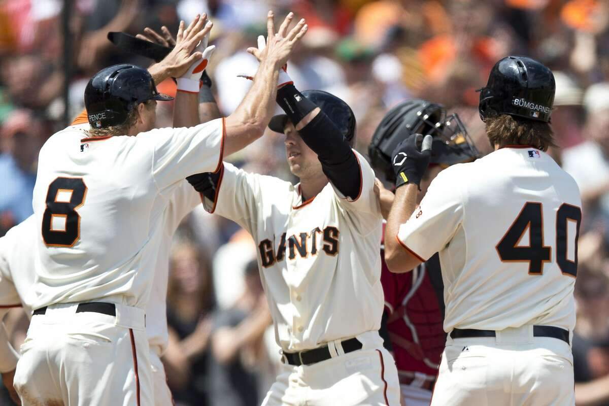 Buster Posey #28 of the San Francisco Giants is congratulated by Hunter Pence #8 and Madison Bumgarner #40 after hitting a grand slam home run off of Vidal Nunoof the Arizona Diamondbacks during the fifth inning at AT&T Park on July 13, 2014 in San Francisco, California. (Photo by Jason O. Watson/Getty Images)