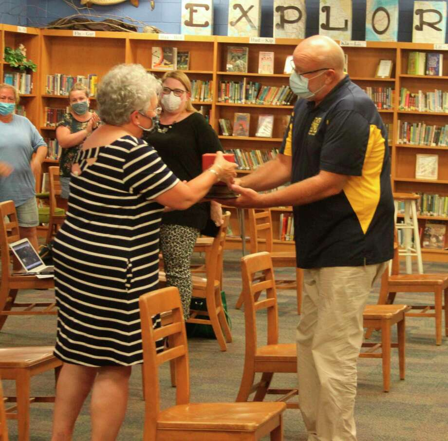 Manistee Area Public Schools superintendent Ron Stoneman presents Ruth Simoneau with a master teacher award to mark her retirement from the district. (Ken Grabowski/News Advocate)